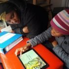 Aphelele reading a story on the Tablet